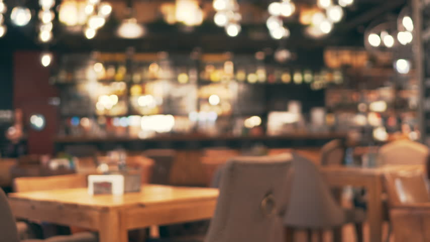 Blurred picture of the interior of a large beautiful restaurant with bright lighting. The waitress is approaching the bar for orders. Hungry visitors enter the restaurant for a delicious lunch | Shutterstock HD Video #1010750579