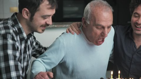 Two affectionate sons celebrate their father's birthday bringing the cake