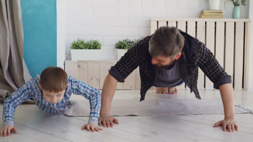 Active handsome father and his joyful son are exercising doing press-up together at home on wooden floor. Happy family, sport and sporty lifestyle concept.