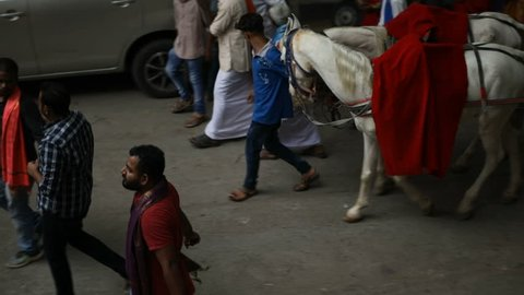 HYDERABAD, INDIA - MAY 07,2018 Colorful indian wedding procession on the street with the bridegroom seated on a horse driven chariot in Hyderabad,India