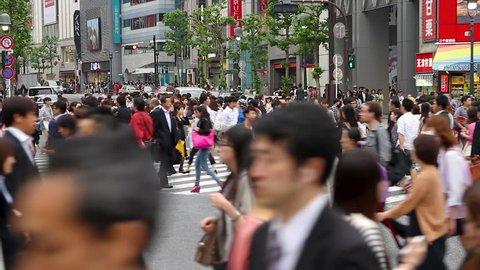 SHIBUYA-KU, TOKYO – MAY 14, 2014: People walking the Shibuya crossing, probably the busiest pedestrian crossing in the world, Tokyo, Japan