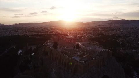 Aerial birds eye view video taken by drone of iconic Acropolis hill and the Parthenon at sunset with beautiful colours, Athens historic center, Attica, Greece