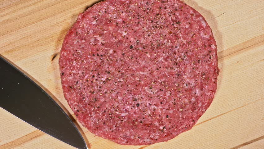 Cook makes meat medallions for burgers. Chef in black food gloves makes cutlet. Cutlets are leveled in steel ring in an even medallion. On top of pouring spices pepper and salt. Meat marbled beef lies