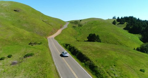Aerial view of car driving down country road through rural grasy hills