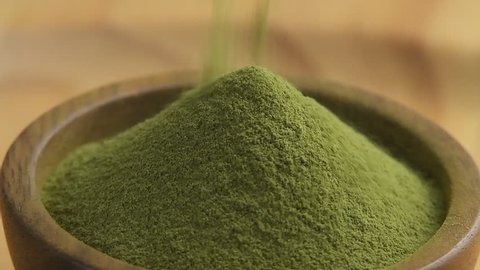 Green tea powder in wood bowl