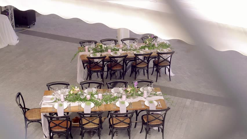 View of wedding decorations outdoor - served table with beautiful flowers. Decorated wedding tables. Wedding reception. Catering for wedding.