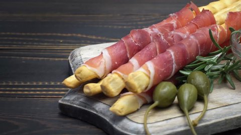 italian grissini with prosciutto, capers and pepper on wooden cutting board