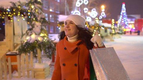 Christmas shopping xmas Christmas  background shoppers. Woman enjoying european christmas market with shopping bags Slow. Shopping girl walking winter city street, Christmas presents, Happy New Year