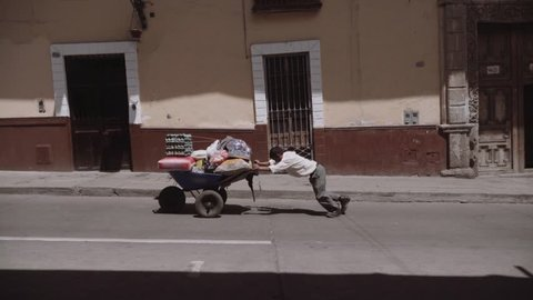 Old man pushing up the wheelbarrow loaded with groceries on the inclined street.