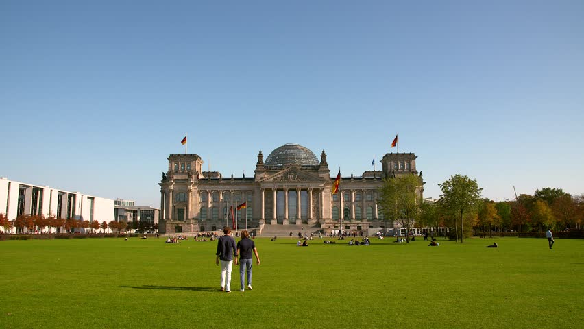 Reichstag Building in Berlin under a blue Sky. People relax on the meadow in front of the Reichstag building where the German Bundestag is located.