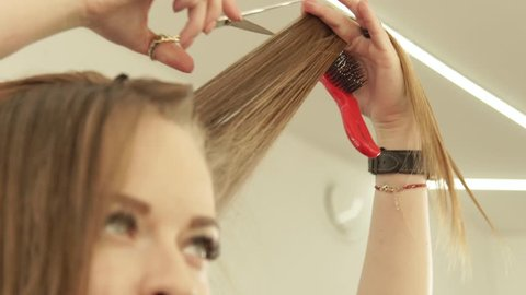 Hairdresser cutting long hair with professional scissors in hairdressing salon. Close up haircutter making woman haircut with scissors in beauty salon