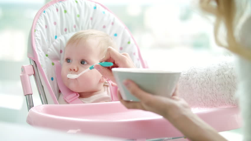 Mother feeding child with baby food. Woman feeding kid with spoon. Cute baby girl eating from porridge bowl. Toddler girl eat pureed food. Mom feed daughter