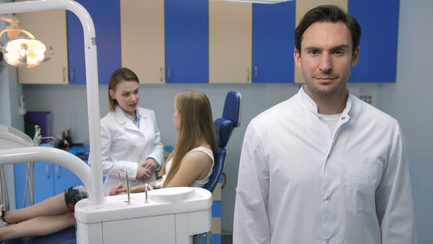 Handsome young adult male dentist standing and smiling to camera with arms crossed in lab coat. Dentist's female assistant talking to patient sitting in dental chair at the background at dental clinic