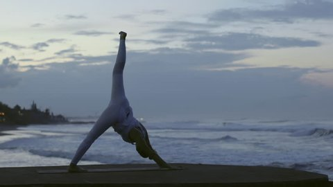 Side view of woman in white leggings and top performing standing split yoga pose on beach in morning