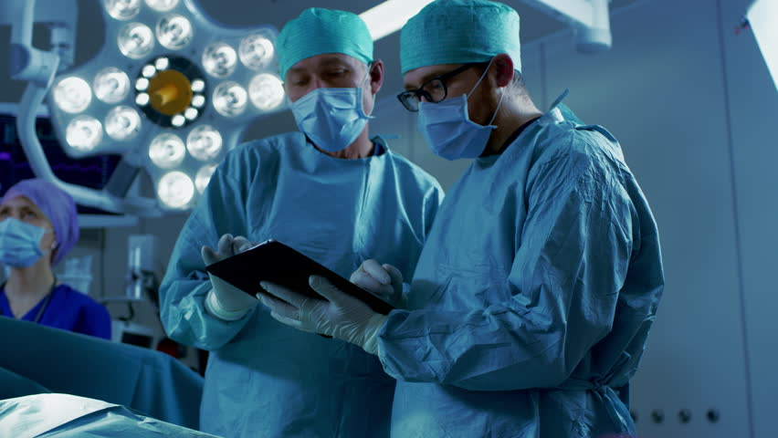 Professional Surgeons and Assistants Talk and Use Digital Tablet Computer while Standing in the Modern Hospital Operating Room.