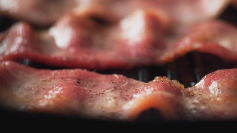 Camera follows adding dried herb on bacon cooked on grill. Shot with high speed camera, phantom flex 4K. Slow Motion.
