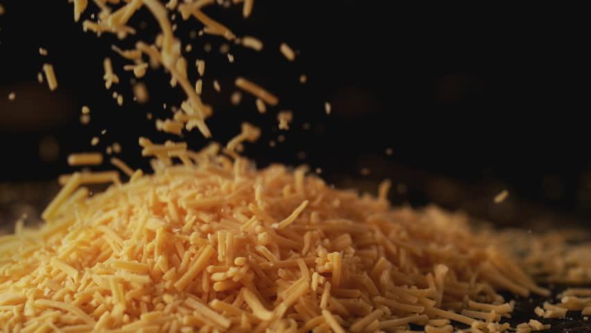 Camera follows shredded cheddar cheese. Shot with high speed camera, phantom flex 4K. Slow Motion.