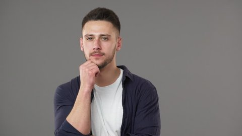 Portrait of smart guy in casual clothing posing with doubting brooding look while thinking or weighing pros and cons, isolated over gray background slow motion. Concept of emotions