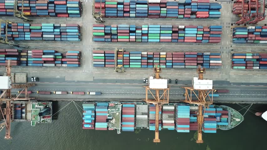 Container ship in export and import business and logistics in Thailand. Shipping cargo to harbor by crane. Water transport International. Aerial view  | Shutterstock HD Video #1011057839