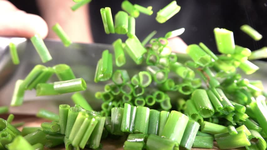 Cutting fresh green onions on a cutting board. | Shutterstock HD Video #1011063659
