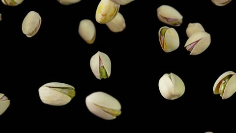 Close up pistachios are flying on a black background in slow motion
