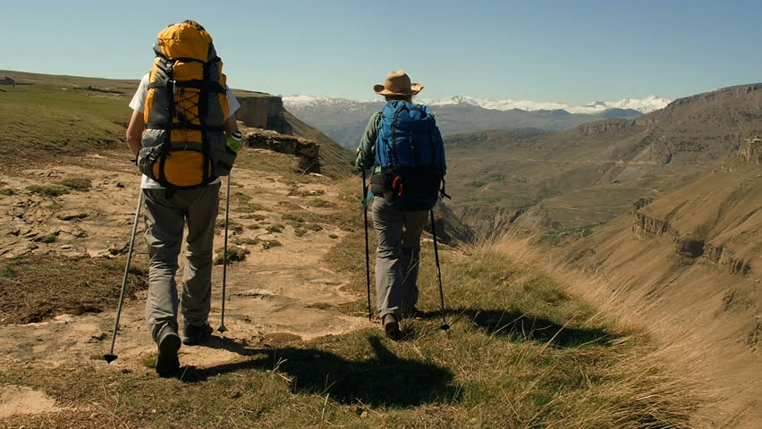 Hikers with backpacks walking  enjoying the view of valley. Two hikers on the trail in the Caucasian mountains. Young active people travelling with backpacks during summer holiday.    Shutterstock HD Video #1011095849
