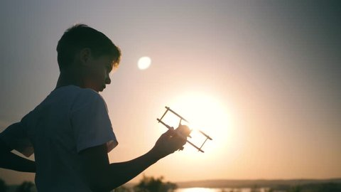 A child is playing with a toy airplane at sunset. Silhouette of a boy holding a toy, hand holding a small airplane. The dream of flying and traveling