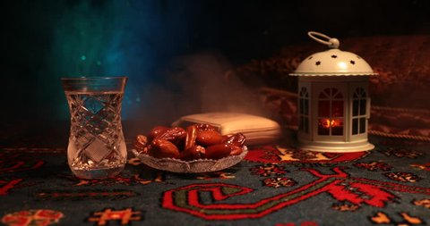 Water and dates. Iftar is the evening meal. Slider view of decoration Ramadan Kareem holiday. Festive greeting card, invitation for Muslim holy month Ramadan Kareem. Dark background. Selective focus