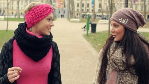 Best friends walking and talking in the city park. Close up. High definition video.