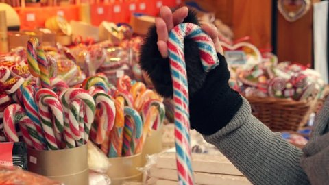 Caucasian woman deciding between colorful lollipops. Christmas time. High definition video.