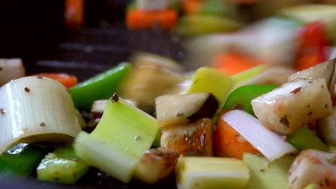 Vegetarian vegetables are fried on a grill pan. Professional chef mixing colored vegetables with a spatula. Macro oil splashes on the pan. Carrot, leek, eggplant, zucchini, sweet pepper, chili pepper.