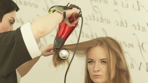 Blonde woman during hairstyling long hair with dryer and hairbrush in hairdressing salon. Close up haircutter drying woman hair with dryer and comb after washing and cutting