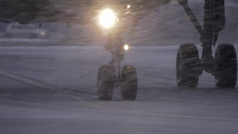 Slow motion shot of airplane wheels moving on runaway. View in evening blizzard