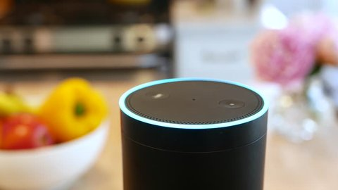 Amazon Alexa closeup in a kitchen.  Pretty flowers and fruit in Background. For editorial use.