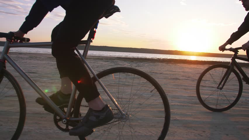 Two young men riding bicycles on the beach on the background of an orange sunsetting sky