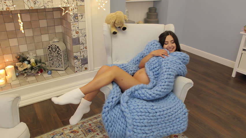 A nude pregnant girl sits in a chair wrapped in a warm knitted plaid. A pregnant girl wrapped in a blanket near the fireplace.