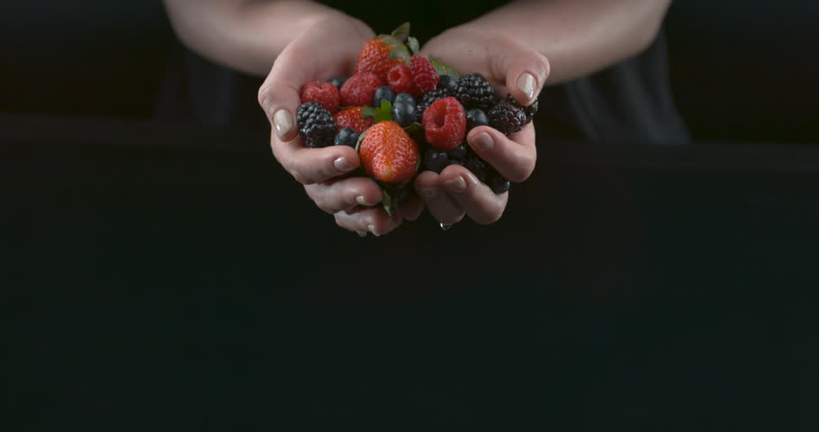 Berries falling out of hands in slow motion. Food cinematic shot. Shot with Phantom Flex.