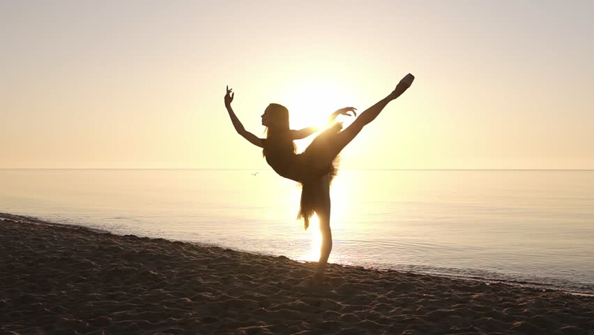 Silhouette of an elegant ballerina in a tutu in the rays of the morning sun. Doing exercises, practicing. Seashore. Slow motion