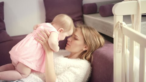 Young mother kissing baby at home. Sweet baby in pink dress in mother embrace. Love and happiness concept. Lovely daughter with mom. Woman hugging baby girl