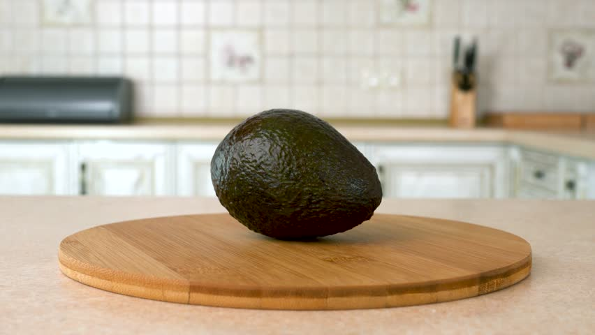 Close up of fresh whole hass avocado. Rotating camera with white kitchen on the background. Dolly-shot.