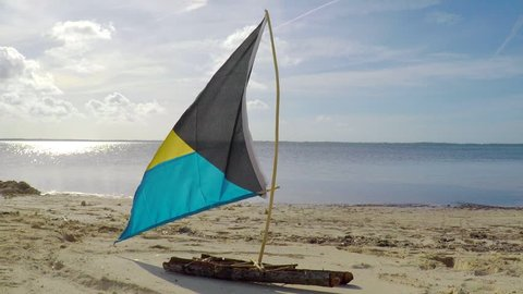 Small wooden sailboat model with Bahamas flag on the beach