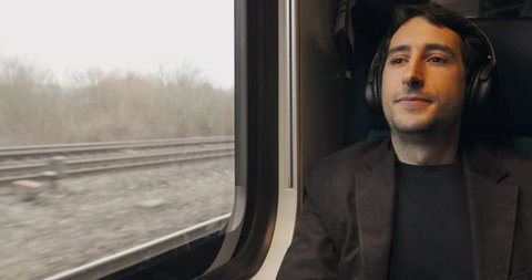 Young man listening to music with headphones while riding train and looking out window
