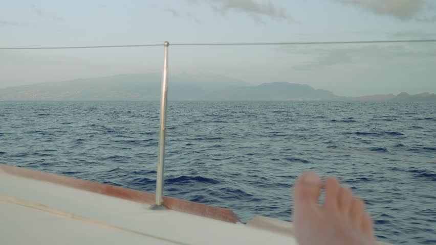 View of Madeira island and man's toes in morning. View from board of sailing yacht   Shutterstock HD Video #1011234509