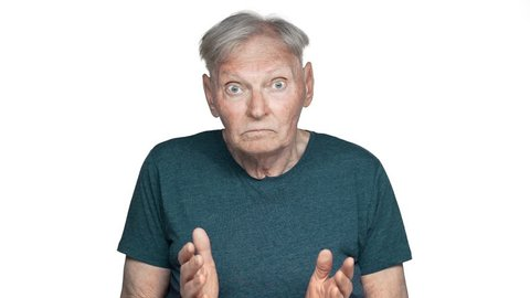 Portrait of embarrassed retired man 80s having gray hair in basic t-shirt shrugging and throwing up hands with helpless emotions in slow motion, isolated over white background