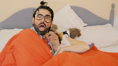 An odd couple (actors in character as kids): a guy and a girl having amazing sex on the bed under a thick blanket. Funny bizarre shot.