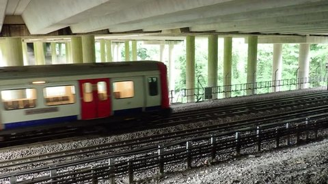 London Underground train passing underneath M25 Motorway bridge, Chorleywood, Hertfordshire
