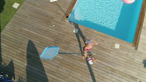 SLOW MOTION, POV, AERIAL: Blonde woman chasing around drone invading her privacy while she sunbathes in her garden. Funny angry girl next door throwing things at remote controlled plane stalking her.