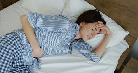 Caucasian young woman in pajama lying on the bed and having strong spasm of stomach pain. Inside
