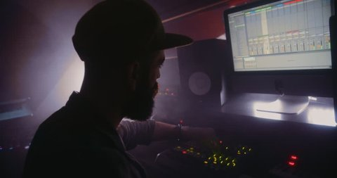 Close-up of music producer working on sound mixer and producing music in recording studio