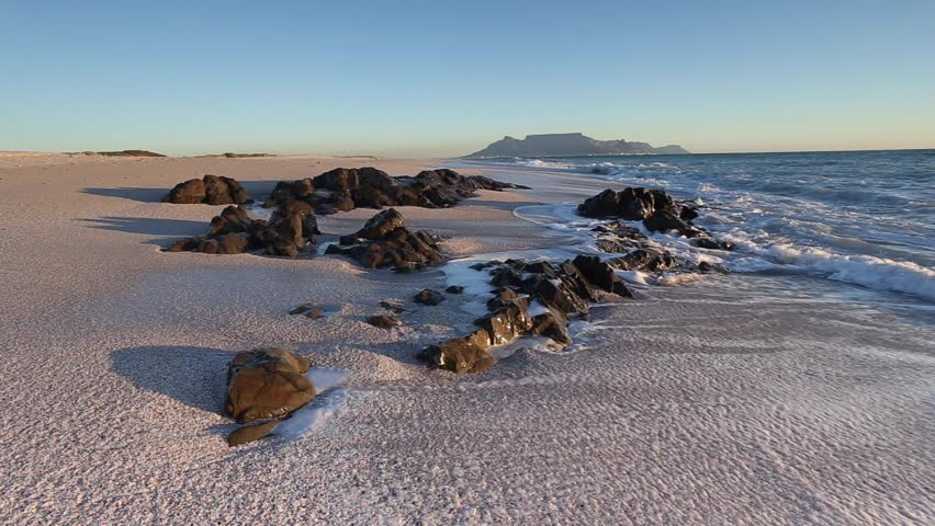 Wide angle view of waves washing up on the sandy beach and crashing against the rocks at Blouberg beach with a view of table mountain in cape town south africa